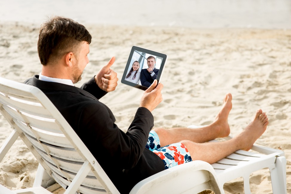 Businessman dressed in suit and shorts having video call with digital tablet on the sunbed at the beach
